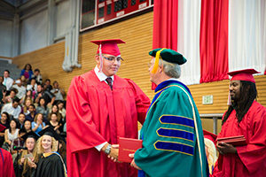Alfredo Diaz-Rodriguez receiving his diploma from Dr. Davis Beyer